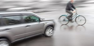 Dangerous city traffic situation with a cyclist and cars in motion blur