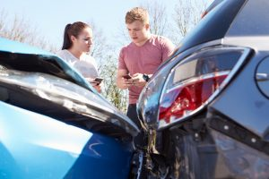 Two Drivers Exchange Insurance Details After Accident and looking concerned