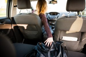 Young woman reaching purse from back seat - rear view